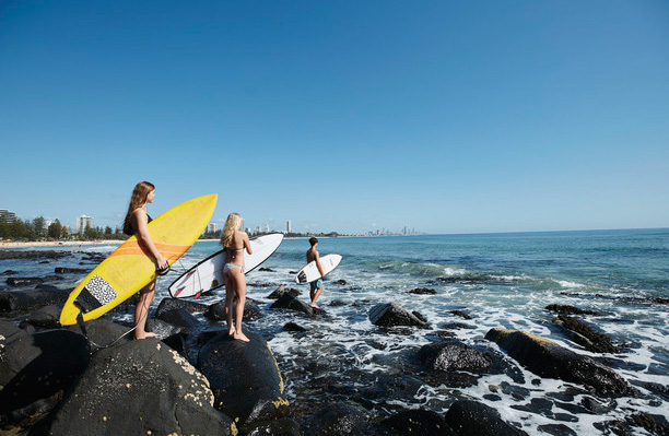 Surfing at Burleigh, standing on rocks