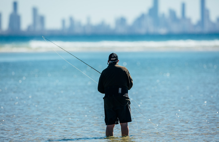 Man fishing at Burleigh with Surfers skyline